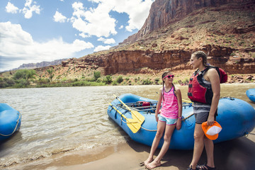 Smiling child and adult women ready to board a large inflatable raft as they travel down the scenic Colorado River near Moab, Utah and Arches National Park