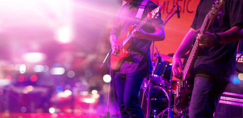 Guitarist and colorful lighting on stage, soft focus