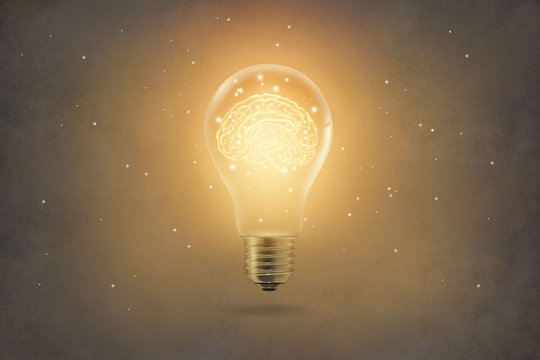 golden brain glowing inside light bulb on paper texture background