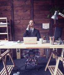 Man working remotely on freelance. Hipster freelancer sitting at wooden desk, making phone calls. Toned image.