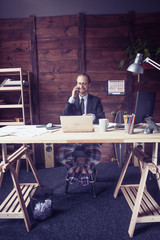 Modern concept of freelance work of young man. Toned image of young modern freelancer sitting at wooden desk, talking on phone.