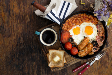 Full English breakfast with cup of coffee on wooden background