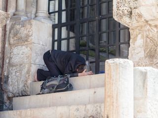 The Pilgrim prays on the steps of the Church of the Holy Sepulchre in the old city of Jerusalem, Israel.