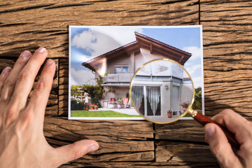 Person Looking House Photograph Through Magnifying Glass