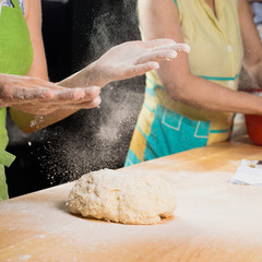 roll dough in flour was sprinkled flour on a wooden board, woman baker. Process of preparing pizza. Cooking time, cooking concept, selective focus