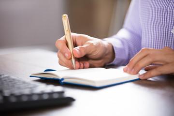 Businessman Writing On Diary