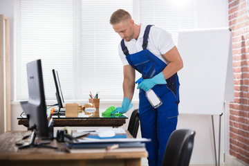 Janitor Cleaning Desk With Cloth In Office