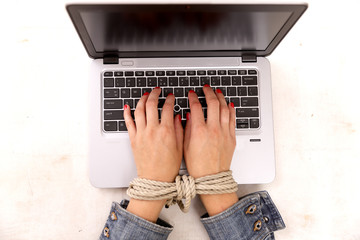 Modern slavery concept. Woman's hand tied working on a computer at work