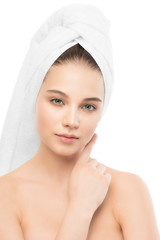 Beautiful young brunette woman with clean face and towel on her head. Beauty spa model girl perfect fresh clean skin. Youth and skin care concept. Isolated.