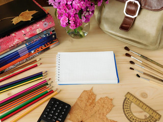 School supplies on a wooden table. Notebook with a blank page in the middle