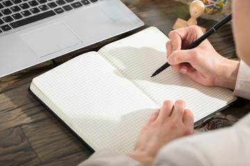 Business Person Writing Down In Checkered Notebook