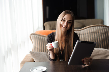 Businesswoman drinking coffee, tea in a coffee shop using a tablet