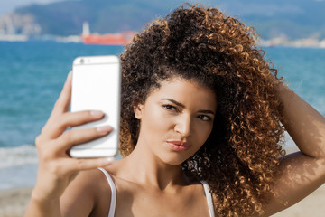 Young and beautiful woman portrait taking selfie near the sea