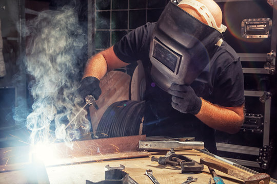 A bald, strong man in a black T-shirt creates with his own hands a mettalical product and brews a metal welding machine, many sparks, fire, and smoke