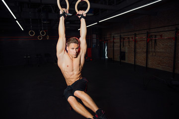 Young fit man pulling up on gymnastic rings.