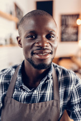portrait of handsome african american male barista looking at camera