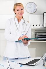 portrait of young female medic with clipboard  in doctor's office