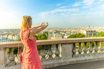 Elegant caucasian woman taking picture with smartphone from Sacred Heart viewpoint. Parisian views from terrace of Sacre Coeur Cathedral, the highest city point of Paris, France. Sunny day.