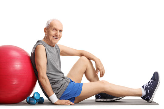 Senior with a pilates ball and dumbbells