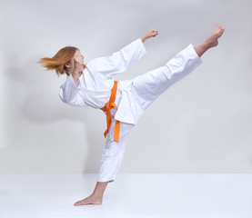 A girl trains a kick with on a light background
