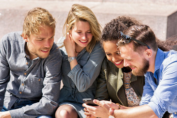 Group of smiling multiracial friends looking photos at mobile phone