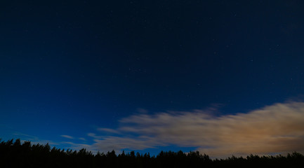 Night landscape with a full moon. Starry sky with clouds.