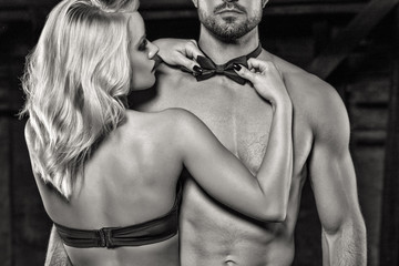 Sensual blonde woman straighten bow tie on naked sexy man black and white