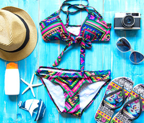 Summer Fashion woman swimsuit Bikini, camera, fish star, sunblock, sun glasses, hat. Travel in the holiday wood blue background.  Summer Concept.