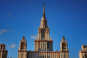 Main building of Lomonosov Moscow State University or MSU at sunset against bright blue sky. Education in Moscow, Russia