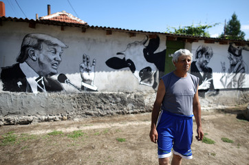 Local villager Kancho, poses next to murals on the wall of his house, depicting him, German Chancellor Merkel and U.S. President Trump in the village of Staro Zhelezare