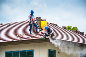 Workers are trimming roof tiles with electric saws.