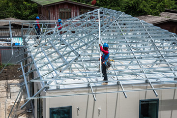 Workers are building a steel roof frame on high.