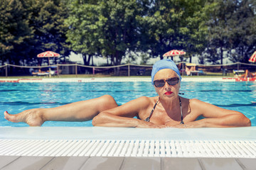 Charming lady in swimsuit posing by the poolside