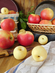 Apples and white nectarines on a wooden table and in wicker baskets. Fresh harvest