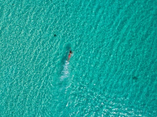 Man swimming in the amazingly blue ocean of Cambodia