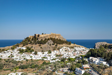Lindos town at the foot of the mountain. Acropolis of Lindos is located on a hill above the town. Bay and harbor with beach.