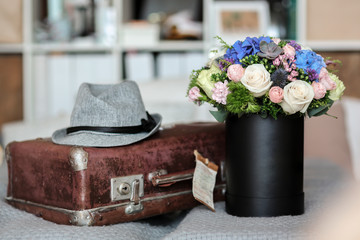 Mixed flowers in the box on the bed with suitcase and a hat
