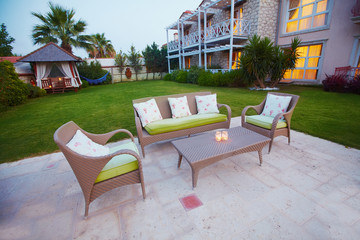 Evening sunset view of small cozy cute boutique hotel, rattan chairs and sofa with pillows.
