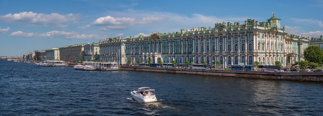 Hermitage palace on the bank of Neva river. The waterfront is moored excursion boats. Saint Petersburg, Russia.