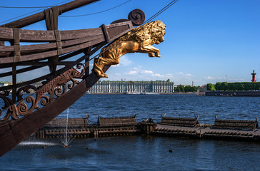 View of the Hermitage and the Rostral column on the opposite Bank of the Neva. In the foreground bowsprit of a sailing ship with a Golden lion. Saint Petersburg, Russia.