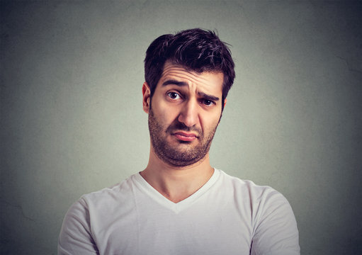 frowning young man thinking expressing doubts and concerns