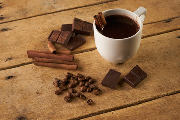 Cup of hot chocolate drink, cinnamon sticks, boken dark chocolate bar and coffee beans on old wooden rustic table