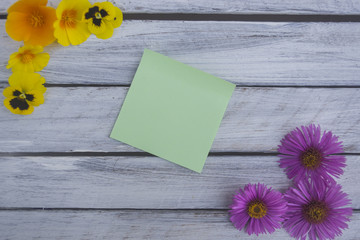 A note on a wooden surface framed by summer flowers 2
