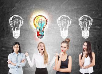 Four businesswomen brainstorming, blackboard