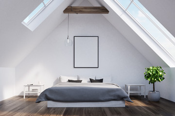 Attic bedroom with a gray bed, poster