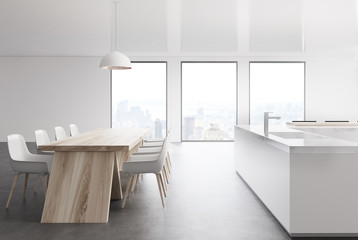 White kitchen with three windows and a table