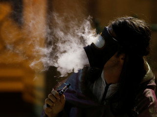 "A performer exhales vapour through a gas mask while smoking an e-cigarette during the contemporary interactive theatre production ""BabelX"" by Maltese director Jacob Piccinino at the Lower Barrakka Gardens in Valletta"