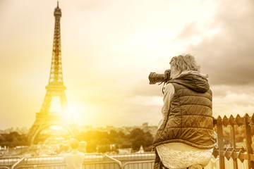 Professional photographer with camera on Place du Trocadero. Traveler woman in Paris, France, Europe. Eiffel Tower on background. Travel and tourism concept. Vintage style shot and burnt film effect.