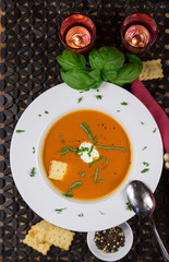 Tomato Soup Served in a Bowl with Basil and Sour Cream Garnish