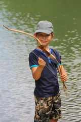 Smiling boy with arrows and bow near water of lake